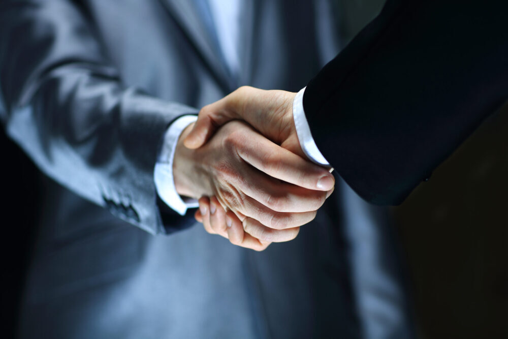 Handshake – Hand holding on black background